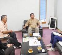 新里社長へ取材を行う、うるま市商工会の比嘉局長と呉屋スーパーバイザー